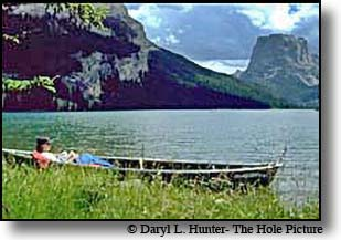 woman reads book in canoe at side of green river lake in the wind river mountains