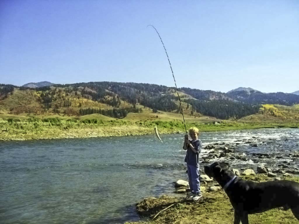 Boy show off fish caught on the Salt River in Alpine Wyoming